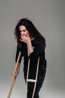 Een mishandelde vrouw in zwarte kleding met zwenkwielen in haar handen op een grijze achtergrond