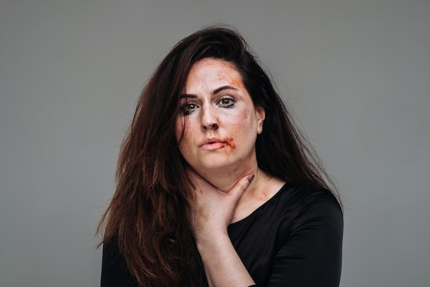 Een mishandelde vrouw in zwarte kleding op een afgelegen grijze achtergrond. geweld tegen vrouwen