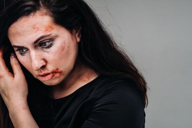 Een mishandelde vrouw in zwarte kleding op een afgelegen grijze achtergrond. geweld tegen vrouwen.