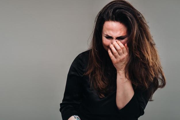 Een mishandelde vrouw in zwarte kleding op een afgelegen grijze achtergrond