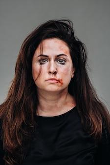 Een mishandelde vrouw in zwarte kleren op een geïsoleerde grijze muur. geweld tegen vrouwen.