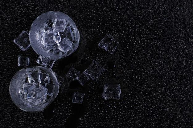 Een mistig glas en ijs ligt op een zwarte achtergrond