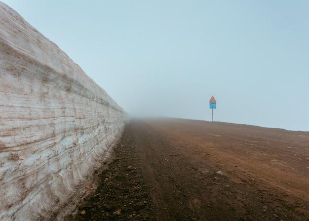 Een mistige modderige weg naast een muur en verkeersborden