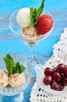 Een mix van aardbeien-, vanille- en karamelijs geserveerd in een glazen beker op een houten tafel