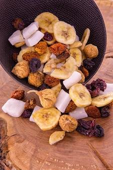 Een mix van gesneden gedroogd fruit en bessen, noten die uit een donkere beker op een houten tafel morsen