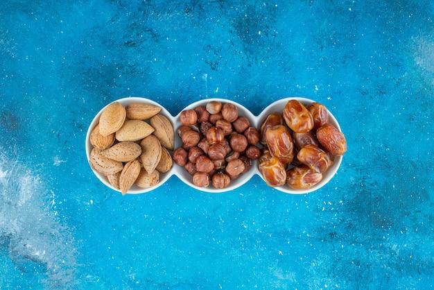 Een mix van noten in een kom op het blauwe oppervlak
