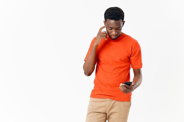 Een mobiele telefoon in de hand van een man met een afrikaans uiterlijk op een lichte achtergrond. hoge kwaliteit foto