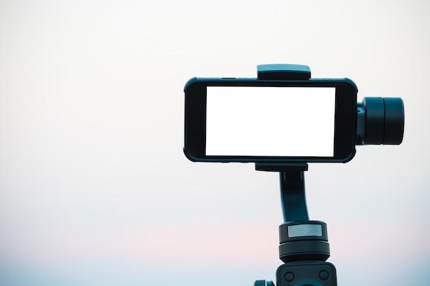 Een mobiele telefoon of smartphone met een wit scherm is uitgerust met een cardanische ophanging, een trillingsstabilisator voor het maken van foto's.