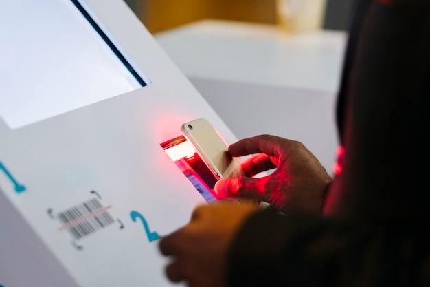Een mobiele telefoon scant een qr-code op een informatiecomputer