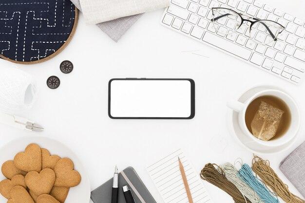 Een mobieltje, een toetsenbord, een kopje thee en koekjes, wat draad en papier