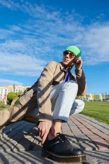 Een mode van mooie man model poseren in de straat van de stad. dragen in klassieke en vrijetijdskleding.