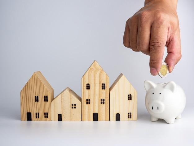 Een model houten huis en een mannenhand met een muntstuk. huisvesting bedrijfsconcept.