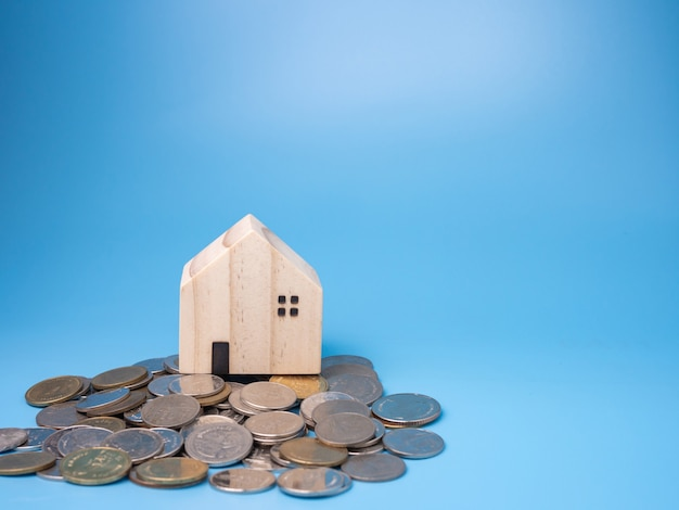 Een model houten huis en een stapel munten op blauw