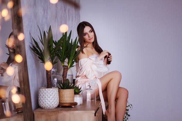 Een model in een nachthemd zit en streelt haar haar. cosmetica en persoonlijke verzorging