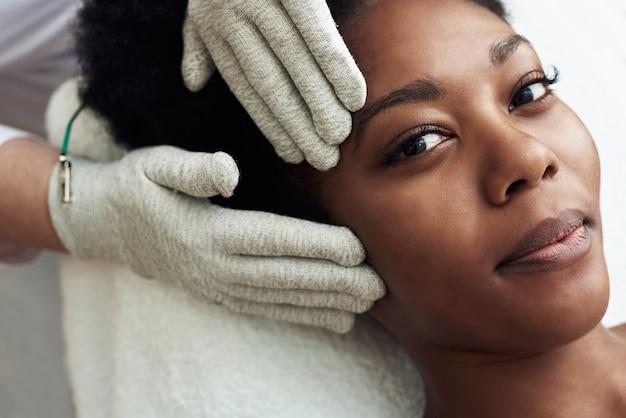 Een model met een donkere huidskleur ligt op de bank bij de schoonheidsspecialiste. microstroom therapie