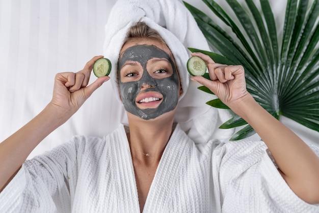 Een model poseert in een badjas terwijl ze komkommers voor een masker in haar handen houdt, met een masker van natuurlijke klei