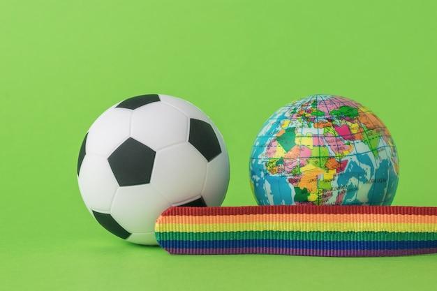 Een model van de wereld, een voetbal en een lgbt-lint op een groene achtergrond. het concept van lgbt in het voetbal. ruimte voor tekst.