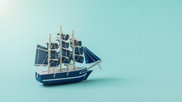 Een model van een grote zeilboot op een blauwe ondergrond in de zon. het concept van reizen en avontuur.