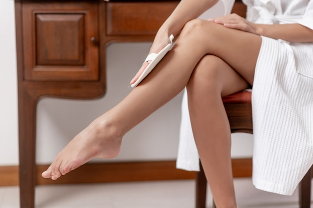 Een model veegt haar benen af met een boender