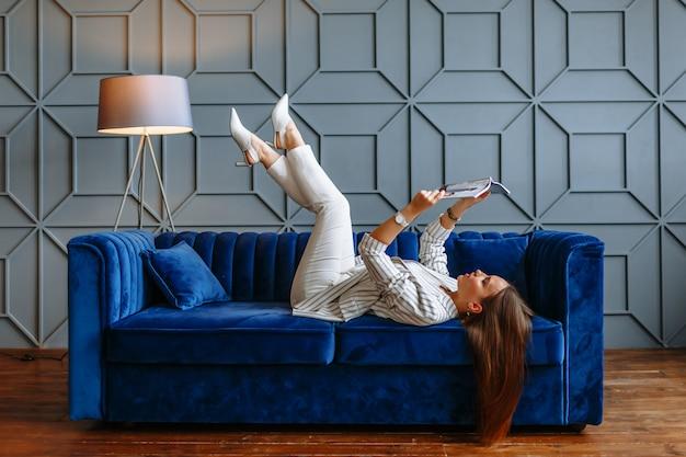 Een model vrouw in een pak met een tijdschrift op een blauwe sofa