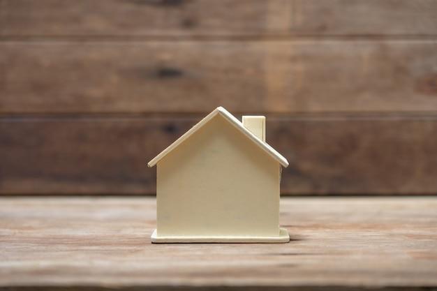 Een modelhuis op hout. onroerend goed concept