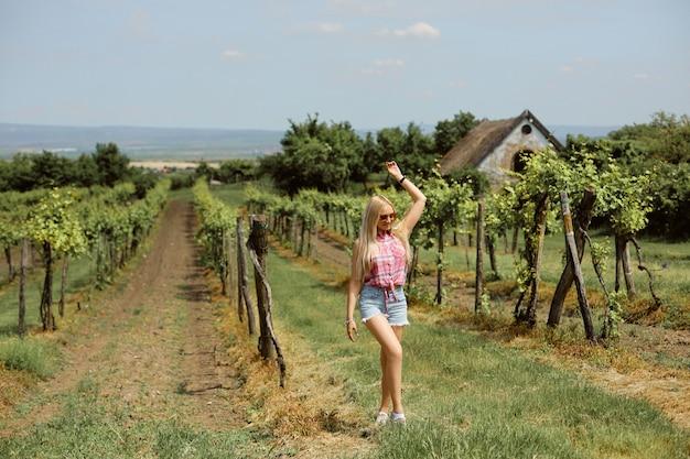 Een modelmeisje in een roze overhemd en spijkerbroek loopt door de wijngaard op het platteland. zomer reizen concept