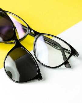 Een modern donker zonnebrilpaar vooraanzicht op wit-geel