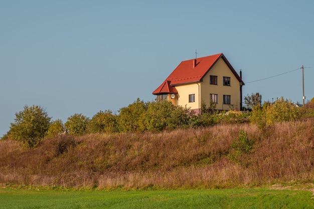 Een modern geel huisje met een rood dak op een groene heuvel.