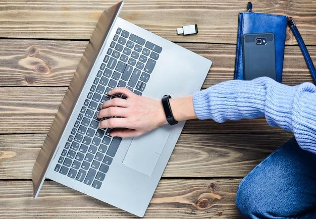Een modern jong meisje zit op een houten vloer en geniet van een laptop. generatie z. het concept van freelancen. werk ruimte. bovenaanzicht