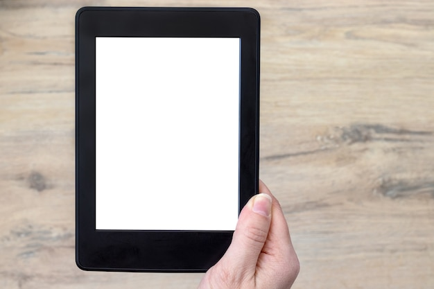 Een modern zwart elektronisch boek met een wit leeg scherm in vrouwelijke hand tegen een vage houten vloerachtergrond. mockup tablet close-up