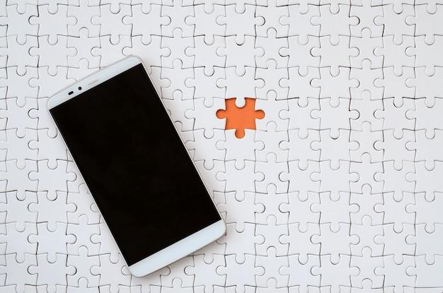 Een moderne grote smartphone met een aanrakingsscherm ligt op witte puzzel