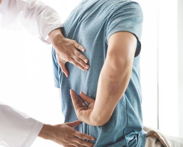 Een moderne revalidatiefysiotherapeut aan het werk met een man-cliënt