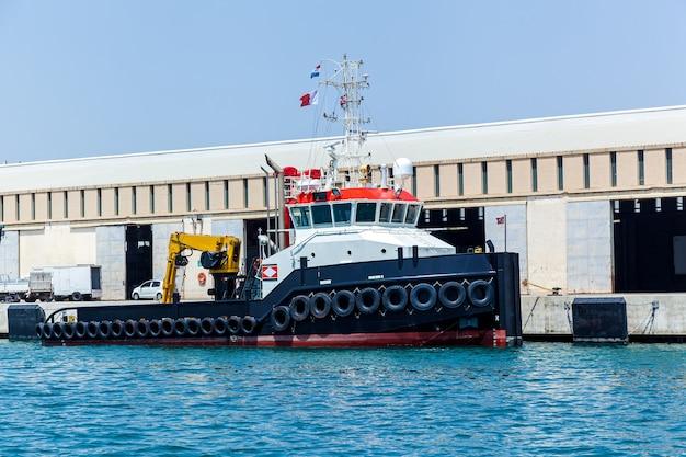 Een moderne sleepboot afgemeerd aan de pier van een industriële haven op zonnige zomerdag op de achtergrond van blauwe lucht.