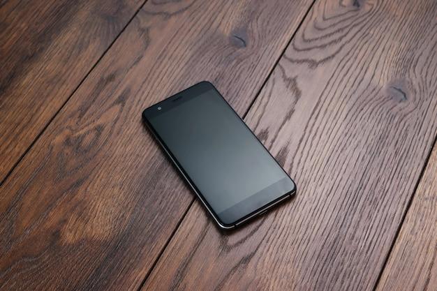 Een moderne smartphone rust op een bruine houten tafel. copyspace.