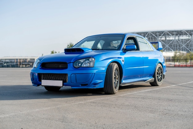Een moderne snelle blauwe raceauto op de baan op de zomeroefendag