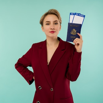 Een moderne trendy lachende vrouw in rood pak met vliegtickets en een paspoort in haar hand.