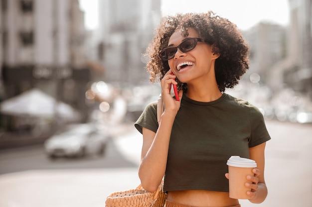 Een moderne vrouw. een donkere jonge vrouw in zonnebril met een smartphone