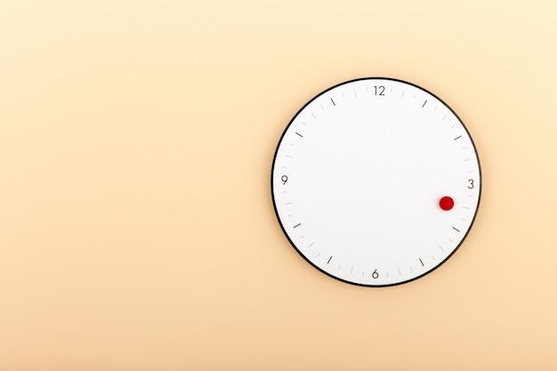 Een moderne witte klok die op oranje muur hangt