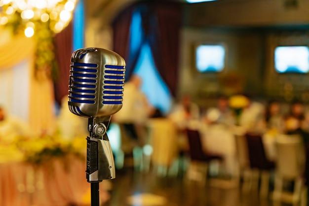 Een moderne zangmicrofoon staat midden in de zaal.
