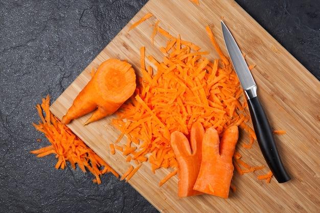 Een modetrend is het eten van misvormde en lelijke groenten. geraspte wortelen op een snijplank.