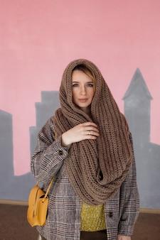 Een modieus en stijlvol meisje in modieuze vintage kleding met een handtas poseert tegen de muur.