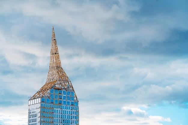 Een modieus glazen gebouw in aanbouw, onafgewerkte torenspits met bossen