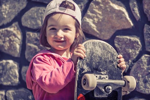 Een modieus meisje houdt een skateboard vast en speelt buiten, de mooie emoties van een kind.