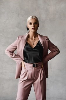 Een modieuze jonge vrouw met blond haar en perfecte make-up in een zwarte blouse en een elegant pak poseren in de studio