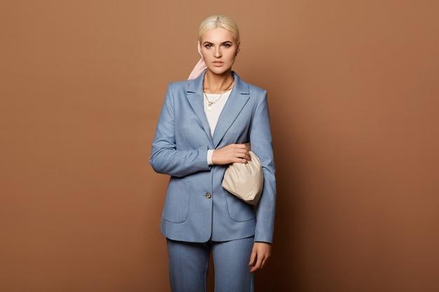Een modieuze jonge vrouw met perfect blond haar in een elegant blauw pak op de beige achtergrond, geïsoleerd met kopie ruimte. concept zakelijke mode en schoonheid