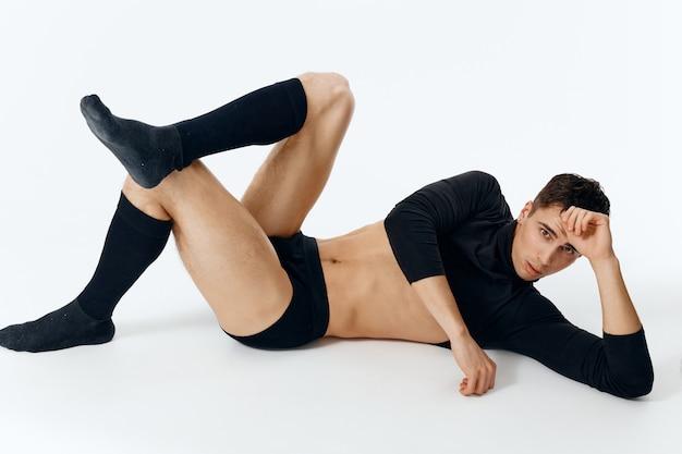 Een modieuze man in een sweateronderbroek en sokken ligt op de grond op een lichte muur