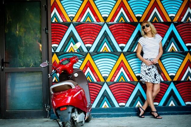 Een modieuze mooie blonde in donkere glazen, staande tegen een lichte muur met geometrische patronen en een rode motorfiets. het concept van recreatie, toerisme en reizen. zomervakantie