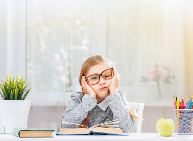 Een moe klein studentenmeisje zit aan een tafel met een stapel boeken.