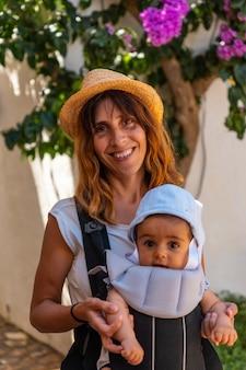 Een moeder die in de zomer met haar baby door de stad sa tuna aan de kust van begur loopt, girona aan de costa brava van catalonië in de middellandse zee