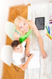 Een moeder die zijn zoon helpt met zijn huiswerk.